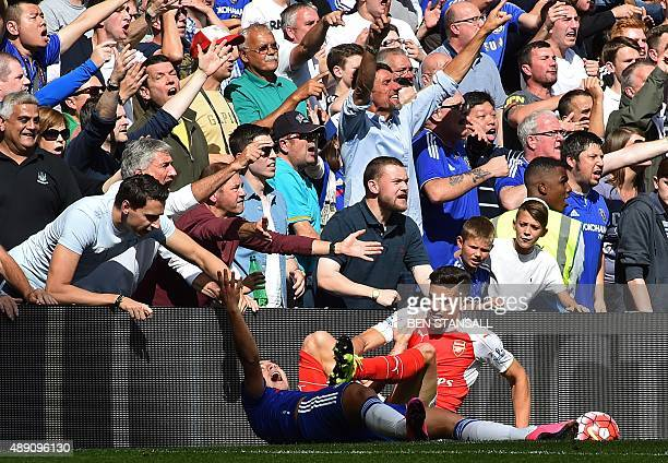 Chelsea's Belgian midfielder Eden Hazard clashes with Arsenal's Brazilian defender Gabriel as the Chelsea fan react during the English Premier League...