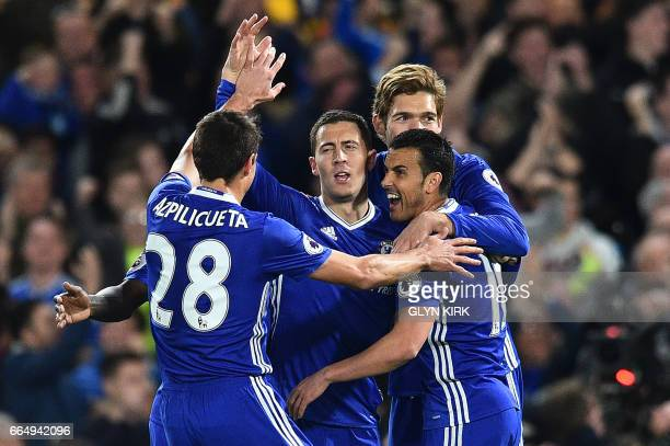 Chelsea's Belgian midfielder Eden Hazard is mobbed by teammates after celebrating scoring his team's first goal during the English Premier League...