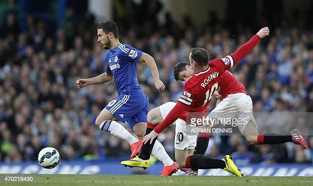 Chelsea's Belgian midfielder Eden Hazard skips past a challenge from Manchester United's English striker Wayne Rooney during the English Premier...
