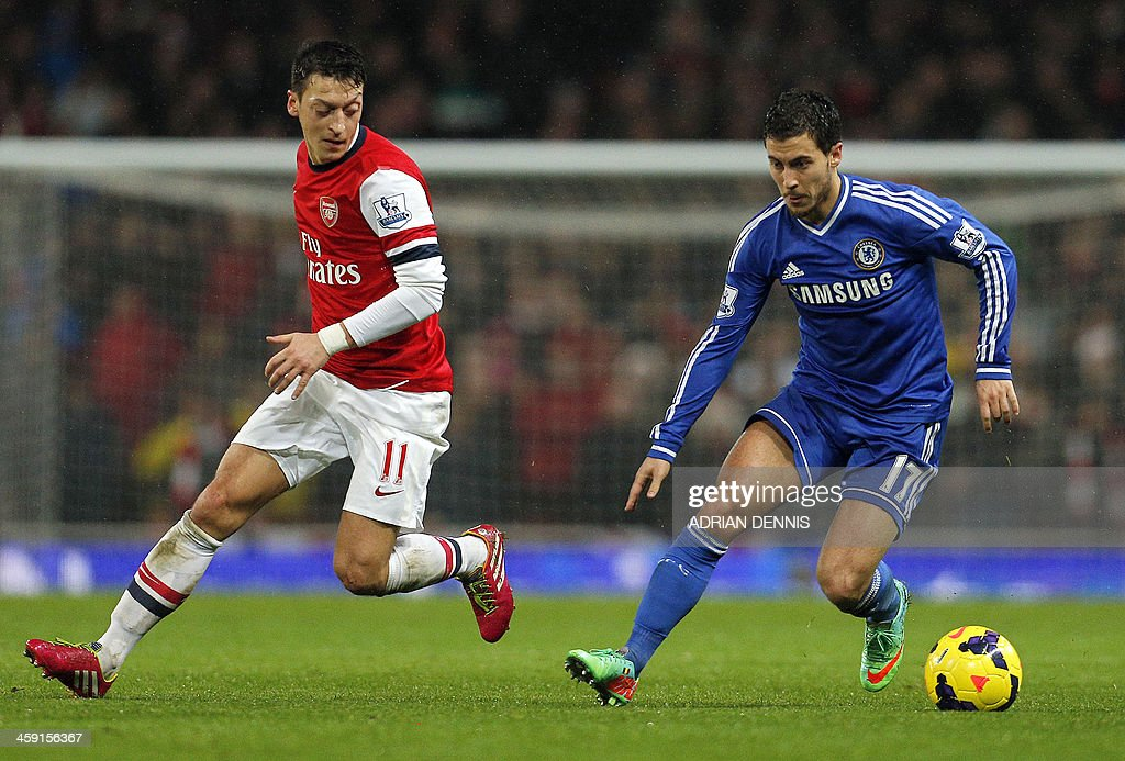 Chelsea's Belgian midfielder Eden Hazard (R) vies with Arsenal's German midfielder Mesut Ozil (L) during the English Premier League football match between Arsenal and Chelsea at the Emirates Stadium in London, on December 23, 2013. USE. No use with unauthorized audio, video, data, fixture lists, club/league logos or 'live' services. Online in-match use limited to 45 images, no video emulation. No use in betting, games or single club/league/player publications.