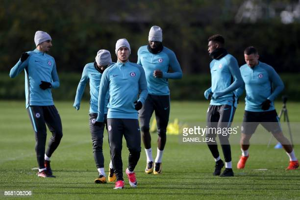 Chelsea's Belgian midfielder Eden Hazard warms up with teammates at a training session at Chelsea's Cobham training facility in Stoke D'Abernon...