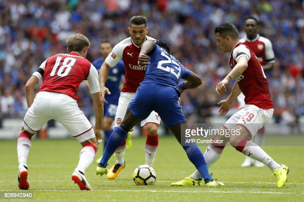 TOPSHOT Chelsea's Belgian striker Michy Batshuayi is challenged by Arsenal's Spanish defender Nacho Monreal and Arsenal's Swiss midfielder Granit...