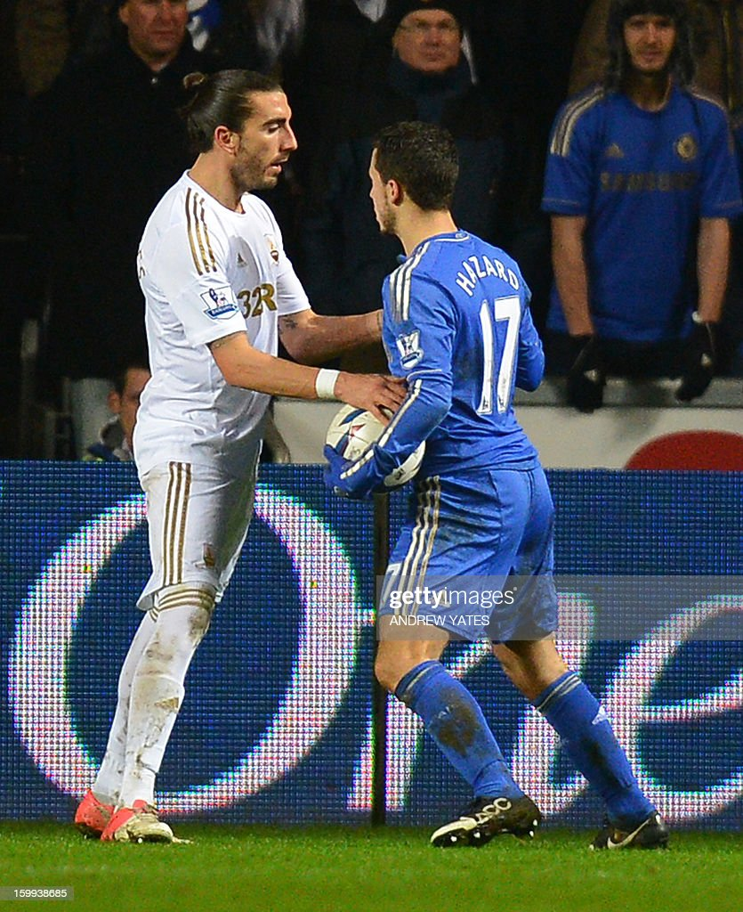 "Chelsea's Belgium midfielder Eden Hazard (R) is confronted by Swansea City's Spanish defender Chico Flores (L) after Hazard was involved in an altercation with a ball boy during the English League Cup semi-final second leg football match between Swansea City and Chelsea at The Liberty stadium in Cardiff, south Wales on January 23, 2013. Hazard was sent off after the incident. USE. No use with unauthorized audio, video, data, fixture lists, club/league logos or ""live"" services. Online in-match use limited to 45 images, no video emulation. No use in betting, games or single club/league/player publications."