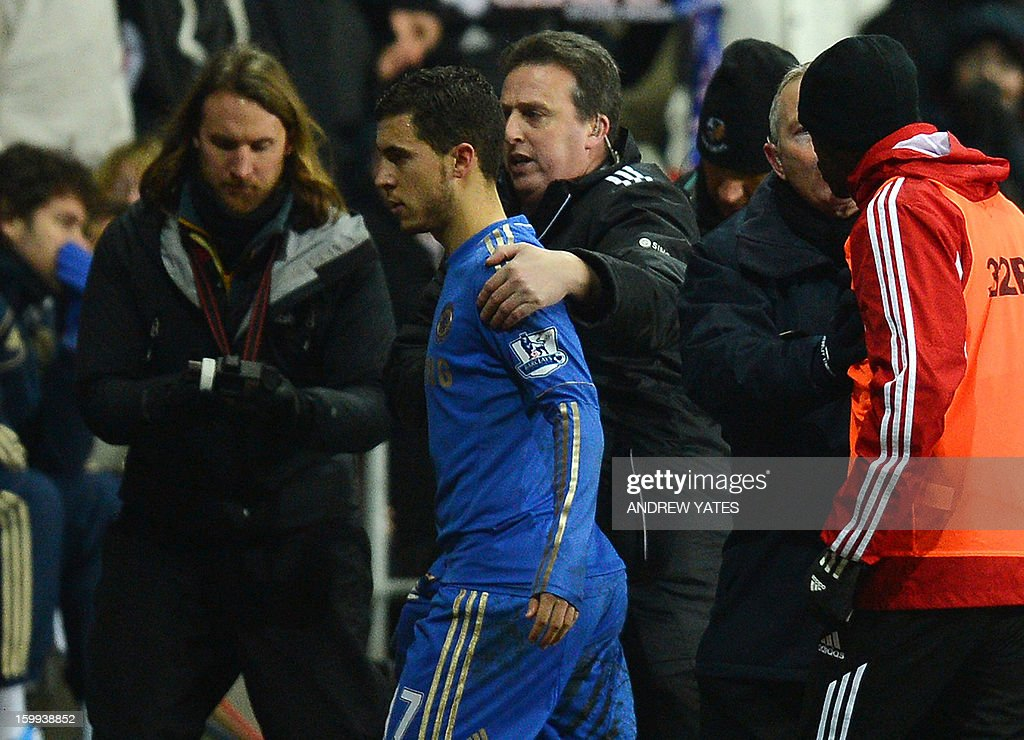 "Chelsea's Belgium midfielder Eden Hazard (C) is escorted off the pitch after being sent off by referee Chris Foy (C) after an incident involving a ball boy during the English League Cup semi-final second leg football match between Swansea City and Chelsea at The Liberty stadium in Cardiff, south Wales on January 23, 2013. USE. No use with unauthorized audio, video, data, fixture lists, club/league logos or ""live"" services. Online in-match use limited to 45 images, no video emulation. No use in betting, games or single club/league/player publications."