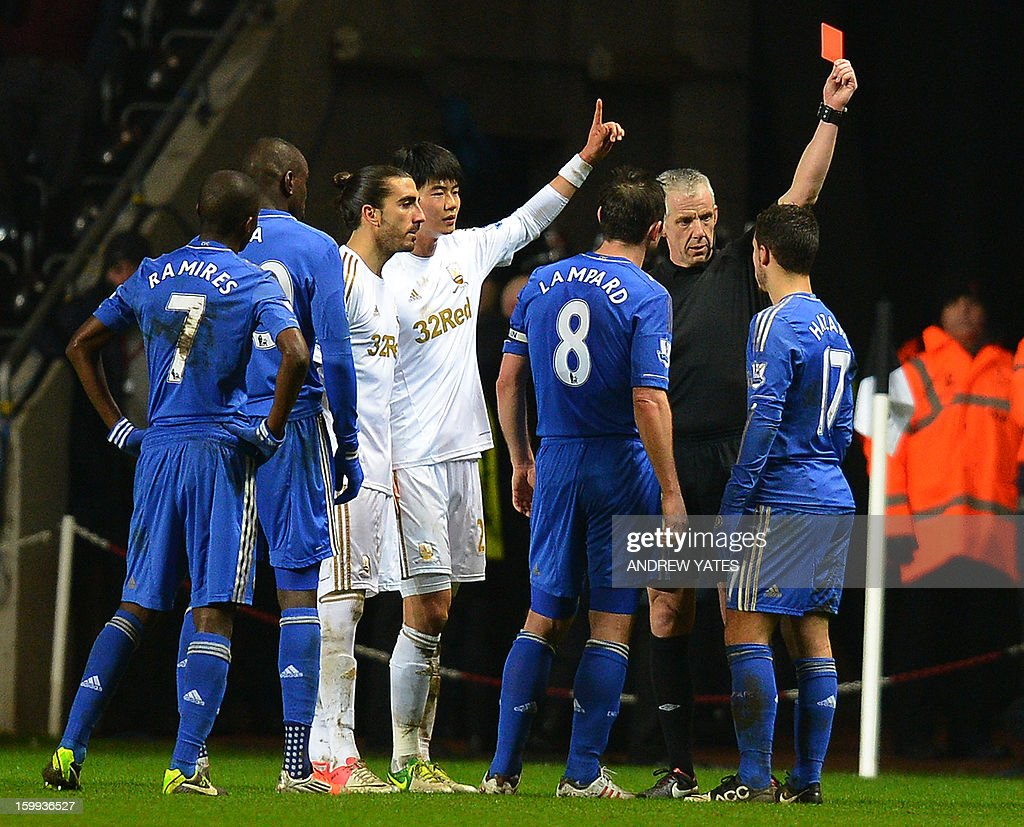 "Chelsea's Belgium midfielder Eden Hazard (R) is sent off by referee Chris Foy after an incident involving a ballboy during the English League Cup semi-final second leg football match between Swansea City and Chelsea at The Liberty stadium in Cardiff, south Wales on January 23, 2013. USE. No use with unauthorized audio, video, data, fixture lists, club/league logos or ""live"" services. Online in-match use limited to 45 images, no video emulation. No use in betting, games or single club/league/player publications."