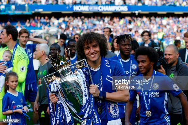 Chelsea's Brazilian defender David Luiz holds the English Premier League trophy as players celebrate their league title win at the end of the Premier...