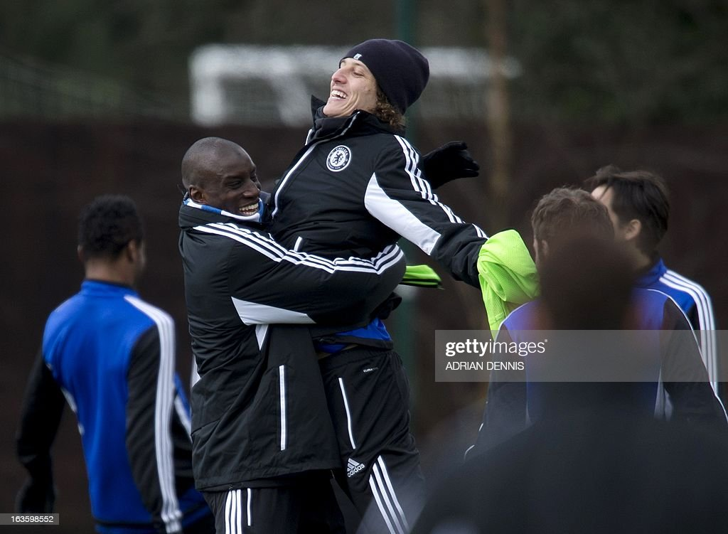 Chelsea's Brazilian defender David Luiz (C) jumps into the arms of teammate Demba Ba (2nd L) during a training session at the club's complex near Cobham on March 13, 2013. Chelsea are to play FC Steaua Bucharest in the UEFA Europa League second-leg match on March 14, 2013. AFP PHOTO / ADRIAN DENNIS