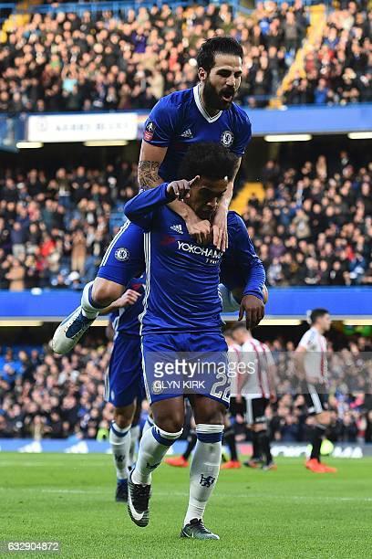 Chelsea's Brazilian midfielder Willian celebrates with Chelsea's Spanish midfielder Cesc Fabregas on his back after scoring the opening goal during...