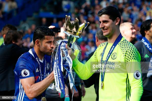 Chelsea's Brazilianborn Spanish striker Diego Costa kisses the English Premier League trophy held by Chelsea's Belgian goalkeeper Thibaut Courtois as...