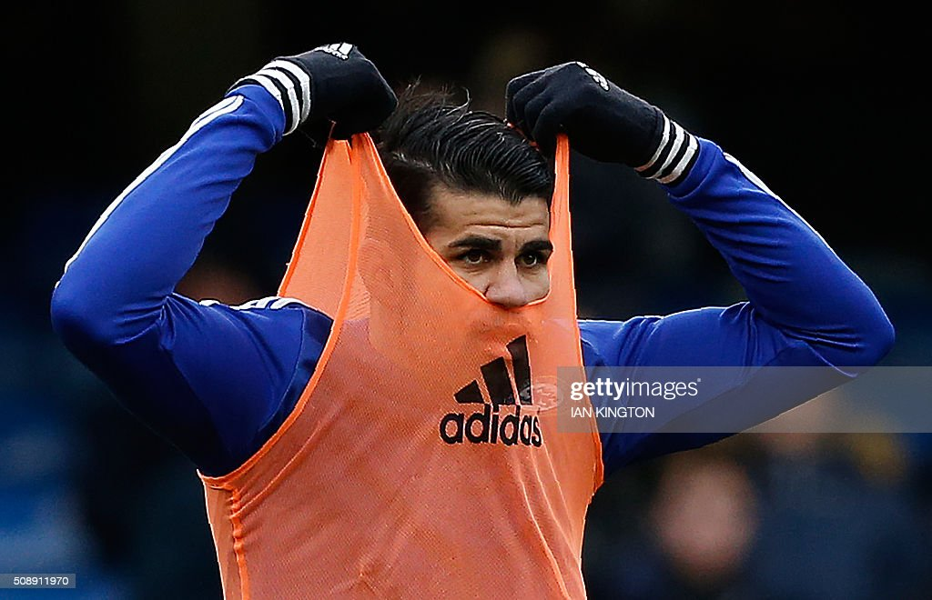 Chelsea's Brazilian-born Spanish striker Diego Costa pulls on his bib as he warms up ahead of the English Premier League football match between Chelsea and Manchester United at Stamford Bridge in London on on February 7, 2016. / AFP / Ian Kington / RESTRICTED TO EDITORIAL USE. No use with unauthorized audio, video, data, fixture lists, club/league logos or 'live' services. Online in-match use limited to 75 images, no video emulation. No use in betting, games or single club/league/player publications. /