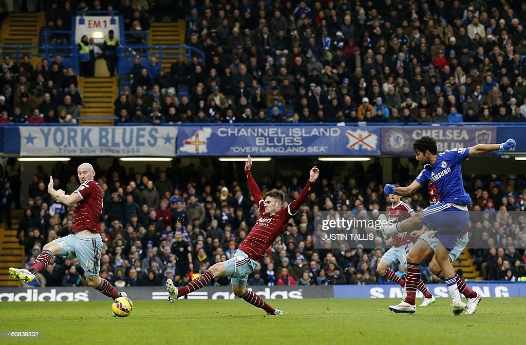 Chelsea's Brazilian-born Spanish striker Diego Costa (R) shoots past West Ham United's English midfielder <a gi-track='captionPersonalityLinkClicked' href=/galleries/search?phrase=Carl+Jenkinson&family=editorial&specificpeople=7935131 ng-click='$event.stopPropagation()'>Carl Jenkinson</a> (2nd L) and West Ham United's Welsh defender <a gi-track='captionPersonalityLinkClicked' href=/galleries/search?phrase=James+Collins+-+Welsh+Soccer+Player&family=editorial&specificpeople=15167252 ng-click='$event.stopPropagation()'>James Collins</a> (L) to score their second goal during the English Premier League football match between Chelsea and West Ham United at Stamford Bridge in London on December 26, 2014. Chelsea won the game 2-0. AFP PHOTO / JUSTIN TALLIS PUBLICATIONS. ==