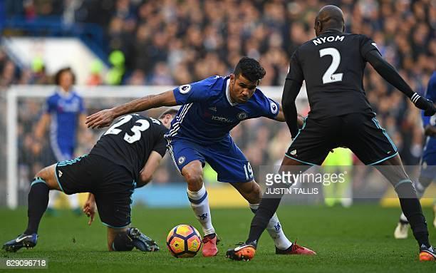 Chelsea's Brazilianborn Spanish striker Diego Costa vies with West Bromwich Albion's Northern Irish defender Gareth McAuley and West Bromwich...