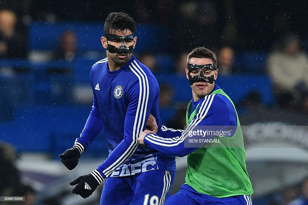 Chelsea's Brazilian-born Spanish striker Diego Costa wears a face mask as he warms up with Chelsea's Spanish defender Cesar Azpilicueta ahead of the English Premier League football match between Chelsea and Newcastle United at Stamford Bridge in London on February 13, 2016. / AFP / BEN STANSALL / RESTRICTED TO EDITORIAL USE. No use with unauthorized audio, video, data, fixture lists, club/league logos or 'live' services. Online in-match use limited to 75 images, no video emulation. No use in betting, games or single club/league/player publications. /