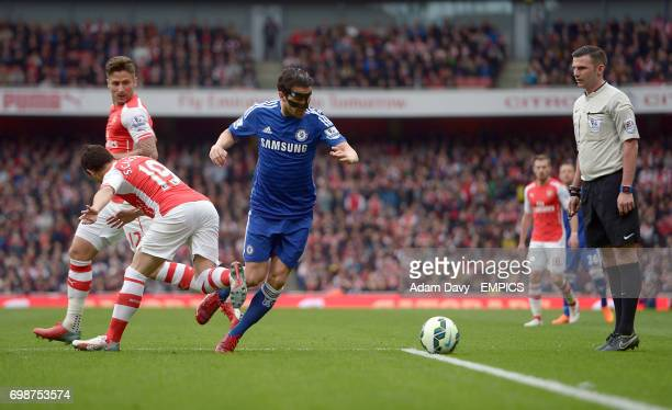 Chelsea's Cesc Fabregas goes down in the penalty area under the challenge of Arsenal's Santi Cazorla but referee Michael Oliver waves away protests...