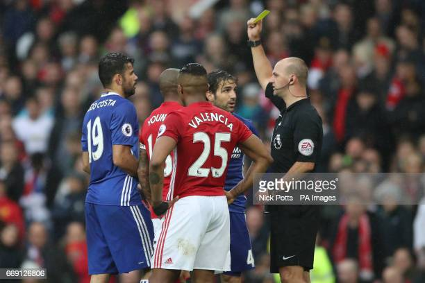 Chelsea's Cesc Fabregas is shown a yellow card by referee Robert Madley during the Premier League match at Old Trafford Manchester