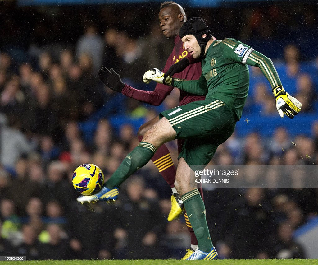 "Chelsea's Czech goalkeeper Petr Cech (R) clears the ball in front of Manchester City's Italian forward Mario Balotelli (back) during an English Premier League football match between Chelsea and Manchester City at Stamford Bridge stadium in London on November 25, 2012. USE. No use with unauthorized audio, video, data, fixture lists, club/league logos or ""live"" services. Online in-match use limited to 45 images, no video emulation. No use in betting, games or single club/league/player publications"