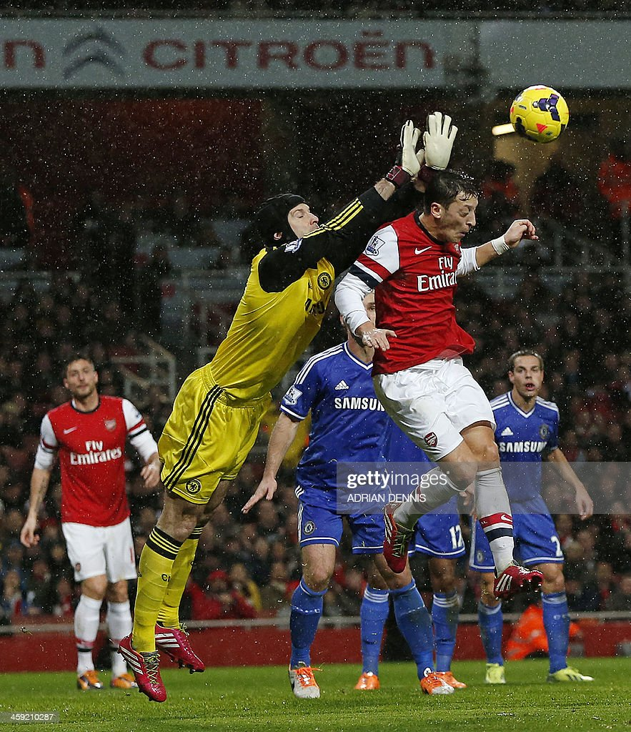 Chelsea's Czech goalkeeper Petr Cech (2nd L) vies with Arsenal's German midfielder Mesut Ozil (2nd R) during the English Premier League football match between Arsenal and Chelsea at the Emirates Stadium in London on December 23, 2013. AFP PHOTO / ADRIAN DENNIS USE. No use with unauthorized audio, video, data, fixture lists, club/league logos or 'live' services. Online in-match use limited to 45 images, no video emulation. No use in betting, games or single club/league/player publications.