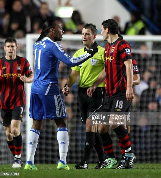Chelsea's Didier Drogba exchanges words with Manchester City's Gareth Barry under the watchful eye of referee Mark Clattenburg