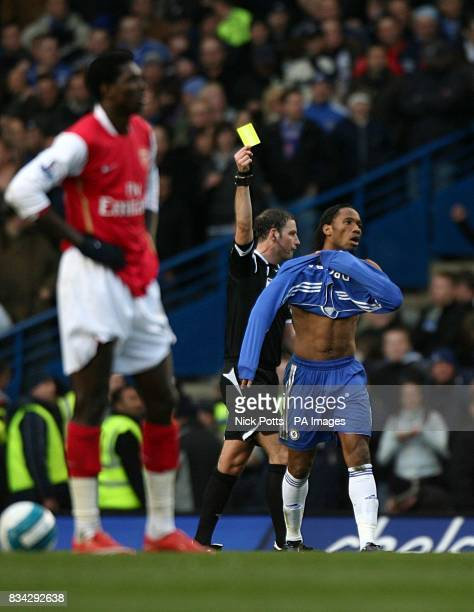 Chelsea's Didier Drogba is booked for taking off his shirt whilst celebrating scoring by referee Mark Clattenburg as Arsenal's Emmanuel Adebayor...