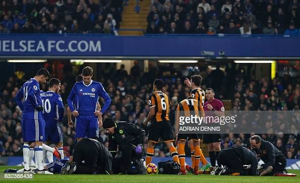 Chelsea's English defender Gary Cahill and Hull City's English midfielder Ryan Mason receive medical treatment after a clash of heads during the...