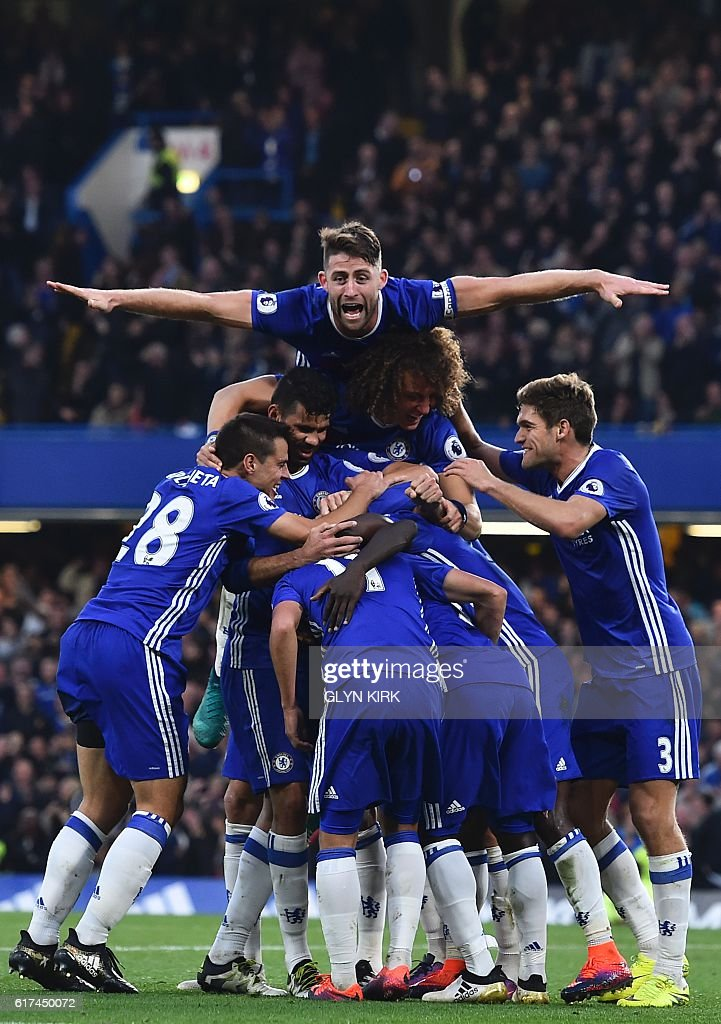 Chelsea's English defender Gary Cahill (top) jumps onto the huddle to join the celebrates after Chelsea's French midfielder N'Golo Kante scored their fourth goal during the English Premier League football match between Chelsea and Manchester United at Stamford Bridge in London on October 23, 2016. / AFP / GLYN KIRK / RESTRICTED TO EDITORIAL USE. No use with unauthorized audio, video, data, fixture lists, club/league logos or 'live' services. Online in-match use limited to 75 images, no video emulation. No use in betting, games or single club/league/player publications. /