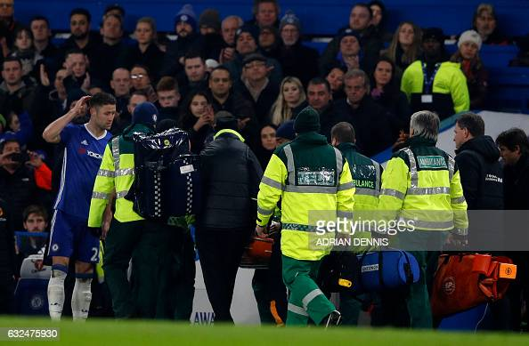Chelsea's English defender Gary Cahill stands by as Hull City's English midfielder Ryan Mason is stretchered from the field after a clash of heads...