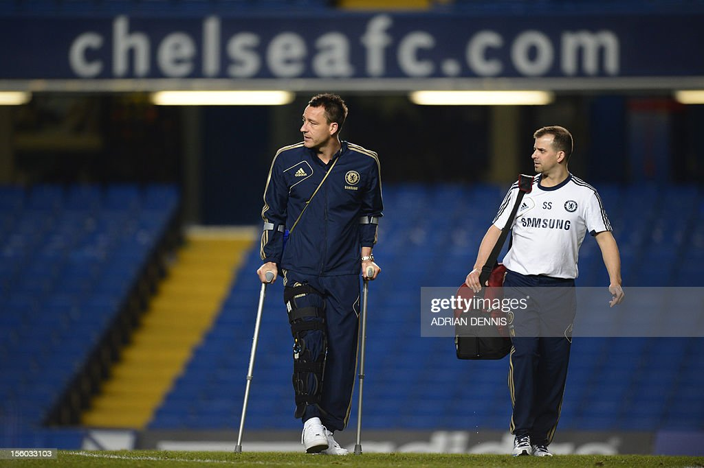 """Chelsea's English defender John Terry (L) is pictured walking on crutches after the English Premier League football match between Chelsea and Liverpool at Stamford Bridge in London, on November 11, 2012. Terry was injured during the match in a collision with Liverpool player Luis Suarez. USE. No use with unauthorized audio, video, data, fixture lists, club/league logos or """"live"""" services. Online in-match use limited to 45 images, no video emulation. No use in betting, games or single club/league/player publications."""