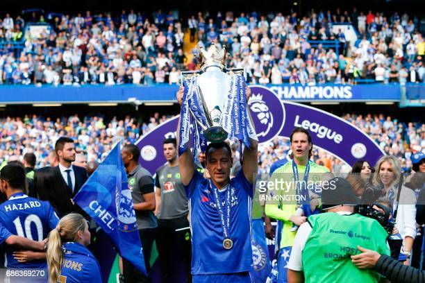 Chelsea's English defender John Terry raises the English Premier League trophy as players celebrate their league title win at the end of the Premier...