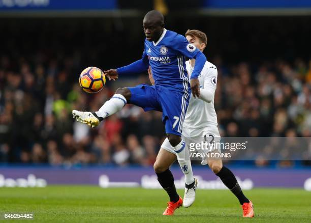 Chelsea's French midfielder N'Golo Kante holds off Swansea City's English midfielder Tom Carroll during the English Premier League football match...
