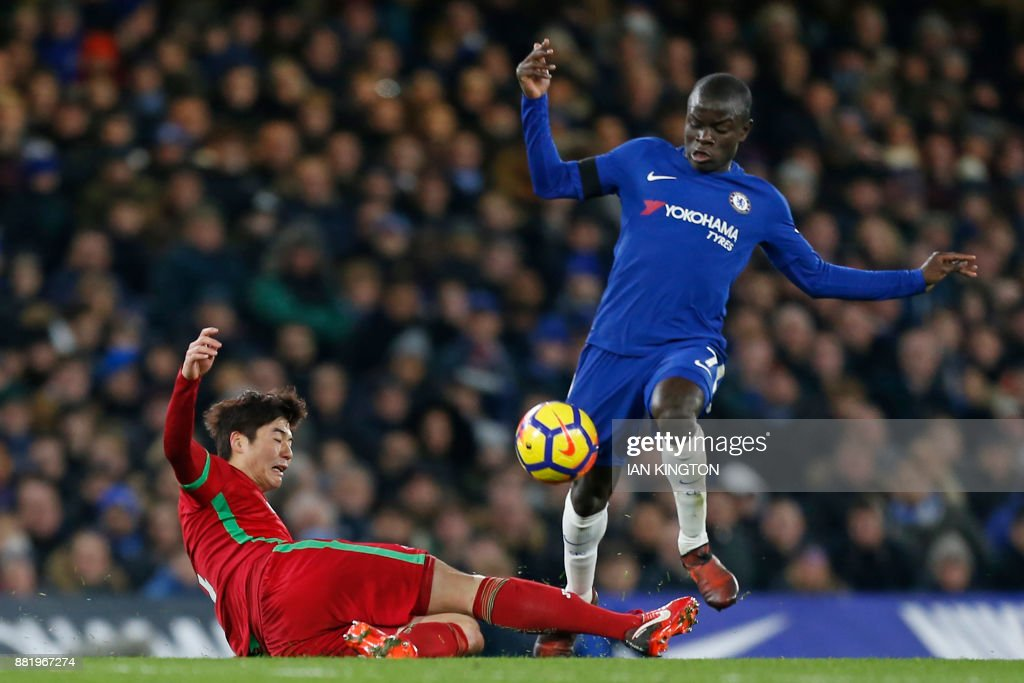 Chelsea's French midfielder N'Golo Kante is tackled by Swansea City's South Korean midfielder Ki Sung-Yueng during the English Premier League football match between Chelsea and Swansea City at Stamford Bridge in London on November 29, 2017. / AFP PHOTO / Ian KINGTON / RESTRICTED TO EDITORIAL USE. No use with unauthorized audio, video, data, fixture lists, club/league logos or 'live' services. Online in-match use limited to 75 images, no video emulation. No use in betting, games or single club/league/player publications. /