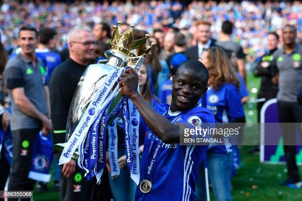 Chelsea's French midfielder N'Golo Kante poses with the English Premier League trophy as players celebrate their league title win at the end of the...