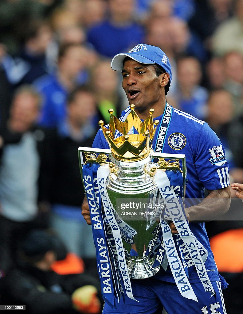 Chelsea's French player Florent Malouda celebrates with the Barclays Premier league trophy after they win the title with a 8-0 victory over Wigan Athletic in the English Premier League football match at Stamford Bridge, West London, England, on May 9, 2010. Chelsea finished the season one pont ahead of 2009 Champions, Manchester United. AFP PHOTO/ADRIAN DENNIS FOR EDITORIAL USE ONLY Additional licence required for any commercial/promotional use or use on TV or internet (except identical online version of newspaper) of Premier League/Football League photos. Tel DataCo +44 207 2981656. Do not alter/modify photo.