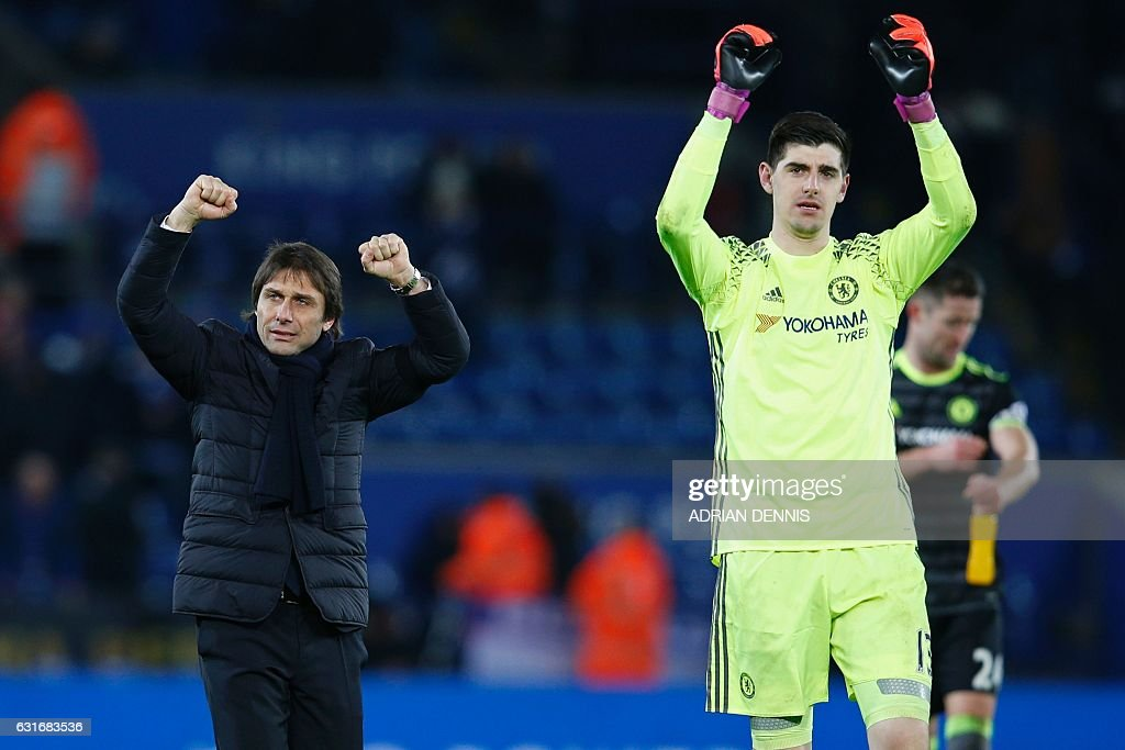 Chelsea's Italian head coach Antonio Conte (L) and Chelsea's Belgian goalkeeper Thibaut Courtois (R) celebrate on the pitch after the English Premier League football match between Leicester City and Chelsea at King Power Stadium in Leicester, central England on January 14, 2017. Cheslea won the game 3-0. / AFP / Adrian DENNIS / RESTRICTED TO EDITORIAL USE. No use with unauthorized audio, video, data, fixture lists, club/league logos or 'live' services. Online in-match use limited to 75 images, no video emulation. No use in betting, games or single club/league/player publications. /