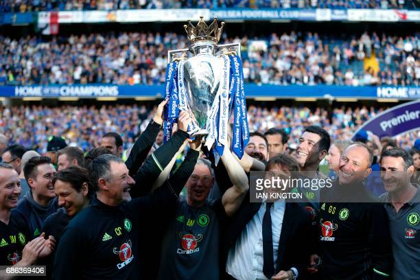 Chelsea's Italian head coach Antonio Conte and his staff raise the English Premier League trophy as players celebrate their league title win at the...
