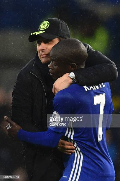 Chelsea's Italian head coach Antonio Conte hugs Chelsea's French midfielder N'Golo Kante on the pitch at the end of the English Premier League...