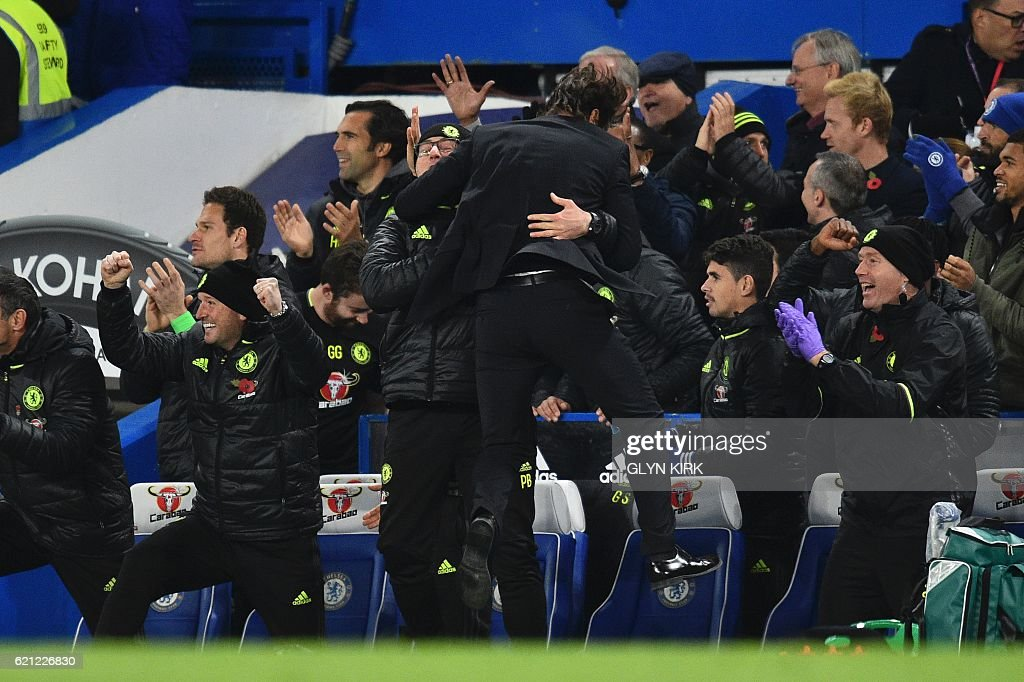 Chelsea's Italian head coach Antonio Conte jumps into the arms of fitness coach Paolo Bertelli as Hazard scores Chelsea's fourth goal during the English Premier League football match between Chelsea and Everton at Stamford Bridge in London on November 5, 2016. / AFP / Glyn KIRK / RESTRICTED TO EDITORIAL USE. No use with unauthorized audio, video, data, fixture lists, club/league logos or 'live' services. Online in-match use limited to 75 images, no video emulation. No use in betting, games or single club/league/player publications. /