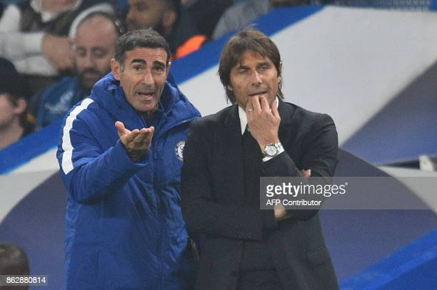 Chelsea's Italian head coach Antonio Conte listens to a member of the backroom staff during a UEFA Champions league group stage football match...