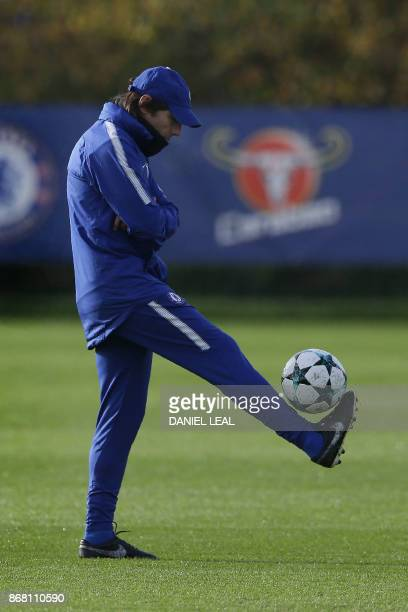 Chelsea's Italian head coach Antonio Conte plays with a football at a training session at Chelsea's Cobham training facility in Stoke D'Abernon...