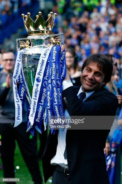 Chelsea's Italian head coach Antonio Conte raises the English Premier League trophy as players celebrate their league title win at the end of the...