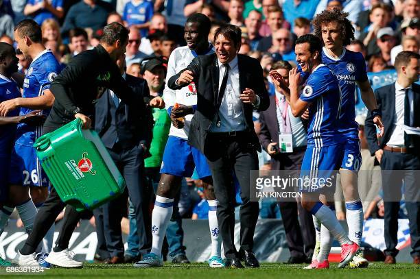 Chelsea's Italian head coach Antonio Conte reacts after being soaked with water as players celebrate their league title win at the end of the Premier...