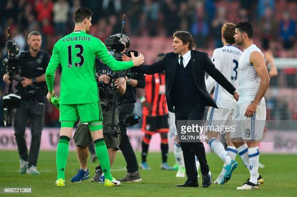 Chelsea's Italian head coach Antonio Conte shakes handswith Chelsea's Belgian goalkeeper Thibaut Courtois at the end of the English Premier League...