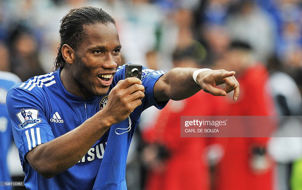 Chelsea's Ivorian striker Didier Drogba waves to fans as he celebrates on the pitch after Chelsea win the title with a 8-0 victory over Wigan Athletic in the English Premier League football match at Stamford Bridge, West London, England, on May 9, 2010. Chelsea finished the season one point ahead of 2009 Champions, Manchester United. Drogba finished as the leading goal-scorer. AFP PHOTO/CARL DE SOUZA FOR EDITORIAL USE ONLY Additional licence required for any commercial/promotional use or use on TV or internet (except identical online version of newspaper) of Premier League/Football League photos. Tel DataCo +44 207 2981656. Do not alter/modify photo.