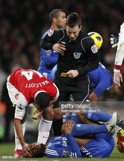 Chelsea's JDidier Drogba is attended to by Arsenal's Theo Walcott and referee Mark Clattenburg