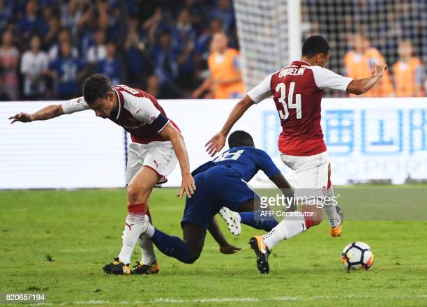 Chelsea's Jeremie Boga is fouled by Arsenal's Laurent Koscielny and Francis Coquelin during their preseason football match in Beijing's National...