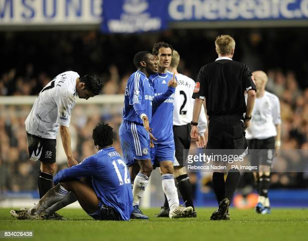 Chelsea's John Mikel Obi sits after he is shown the red card by referee Peter Walton as his teammates complain