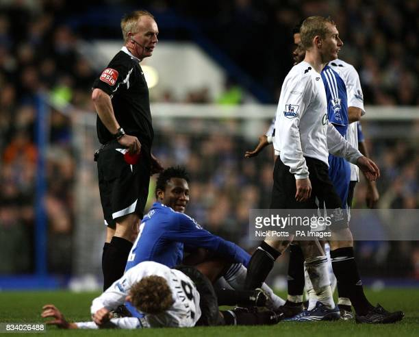 Chelsea's John Mikel Obi sits dejected as referee Peter Walton shows him the red card following a challenge on Everton's Phil Neville