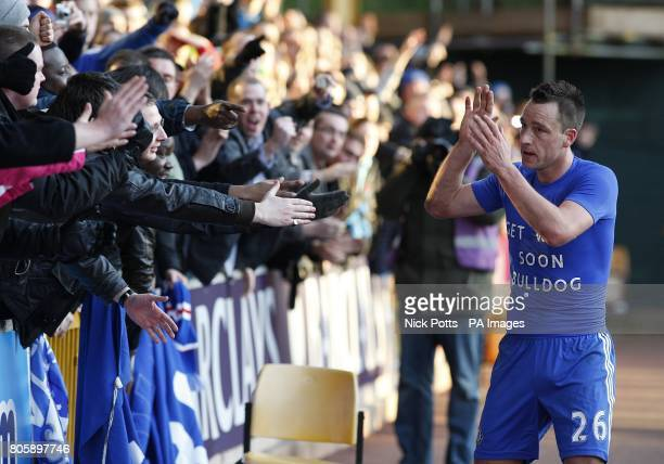 Chelsea's John Terry applauds the fans in the crowd after the final whistle wearing a tshirt displaying the message 'Get well soon Bulldog' which...