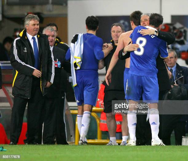 Chelsea's manager Guus Hiddink looks on as Frank Lampard hugs Juventus Coach Claudio Ranieri after the final whistle