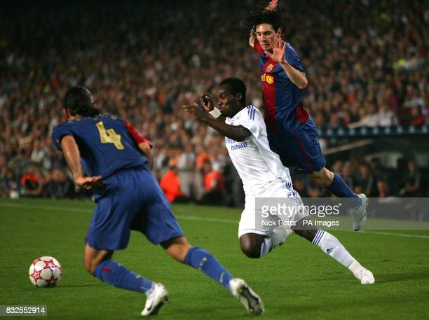 Chelsea's Michael Essien is challenged by Barcelona's Leo Messi and Rafael Marquez