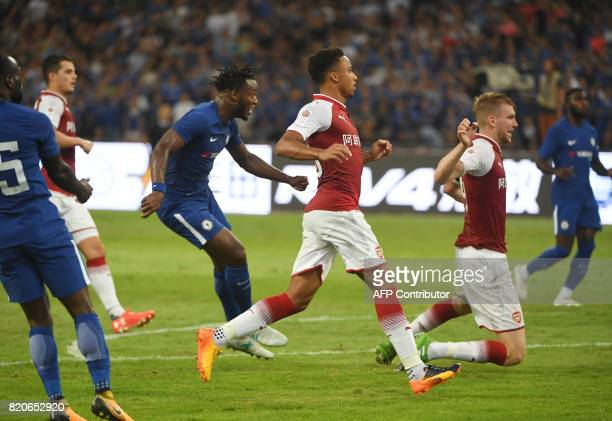 Chelsea's Michy Batshuayi scores as Arsenal's Ainsley MaitlandNiles and Per Mertesacker 2nd R look on during their friendly football match in...